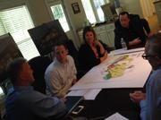 Newland Communities' Senior Vice President Keith Hurand, left, and Newland's Chairman and CEO Bob McLeod, seated at the head of the table, talks to the project team in the temporary office for Wendell Falls about plans underway its first residential neighborhood expected to open in the spring.