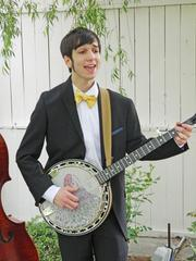 Kyle Gnadinger sang and played the banjo during the Starfish Tumblers' performance at the Warrens' garden party.