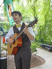Dean Gnadinger sang and played guitar during the party at the DuPont Mansion on Thursday. The brothers were coaxed into learning folk and Bluegrass music by an uncle.