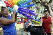 Elenor Piilani Johnson, left, gets a balloon made by Douglas Odani,  owner of Balloon Productions, at the AIDS Walk 2013.
