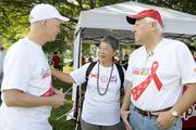 From left, Dr. David McEwan; Jo Chang, advocate for the lesbian, gay, bisexual, and transgender community; and Paul Groesbeck, executive director for Life Foundation, talk at the sponsor booth before the start of the AIDS Walk 2013 at Kapiolani Park on April 14.