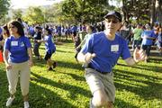 Bank of Hawaii's Mary Bitterman, left, and director Bub Wo participate in a warm-up prior to the Bank of Hawaii's 7th Annual Community Walk at the Honolulu Zoo.