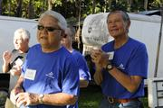Bank of Hawaii board member Don Takaki, left, and Mike Chun cheering on bank employees participating in the Bank of Hawaii's 7th Annual Community Walk at the Honolulu Zoo.