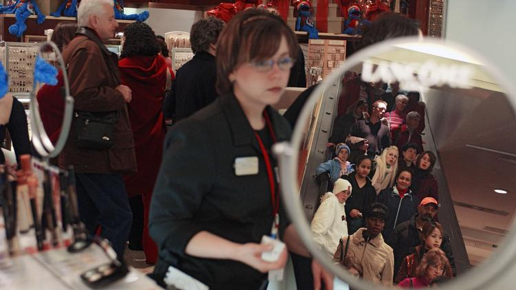 Shoppers are reflected in a mirror on a cosmetics counter at Macy's department store in this file photo.