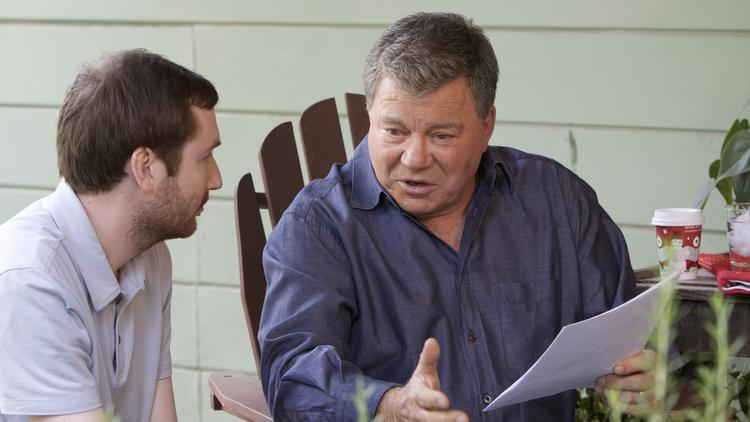 Star Trek actor William Shatner talks with a crew member during a television shoot.