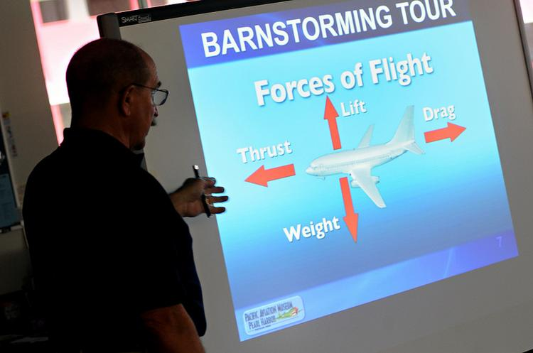 Ken Dewey, founder of the Pacific Aviation Museum's five-year-old Barnstorming program, teaches a class of sixth-grade students about the fundamentals of flight.