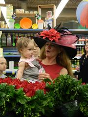 WAVE-TV garden expert Cindi Sullivan greeted Kroger customers, including this little girl, while making an appearance at the Kroger store in Middletown where the Derby rose garland was being made on Friday.