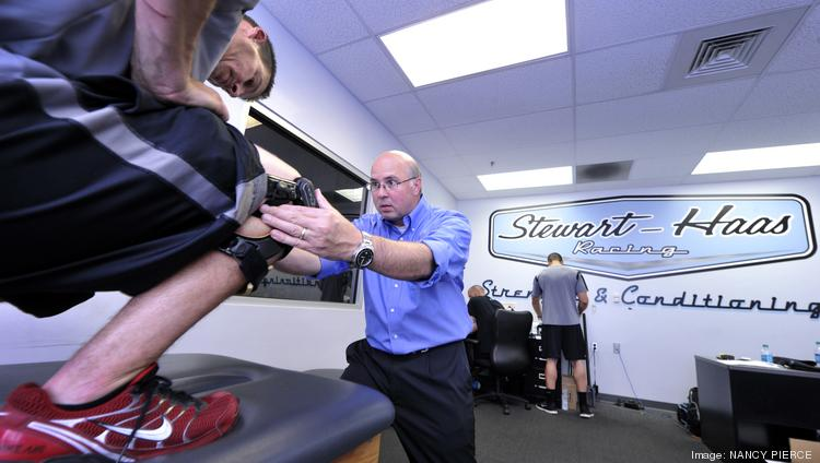 Bill Heisel, a physician's assistant at OrthoCarolina, works with pit crew members in Stewart-Haas Racing's strength and conditioning facility.