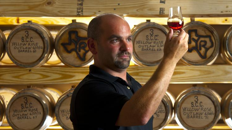 Troy Smith of Yellow Rose looks over whiskey stilled from his Pinehurst distillery.