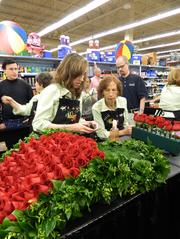 Bev Fairfax, left, and June Domian, members of Kroger's floral team, chose roses to be sewn onto the Derby winner's garland.
