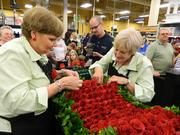 Kroger floral team members Cathy Sheppard, left, and Vel Byrd worked together on the Derby garland as photographers flocked around them.