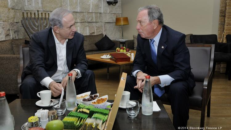 Michael Bloomberg, majority shareholder of Bloomberg LP and former New York mayor, right, speaks with Benjamin Netanyahu, Israel's prime minister, at Ben Gurion International Airport near Tel Aviv, Israel, on Wednesday. The Federal Aviation Administration (FAA) had ordered U.S. airlines to suspend flights to Tel Aviv for 24 hours as Palestinian militants fired a rocket near the city's airport. Bloomberg flew to Israel on an El Al flight to show his support. Photographer: Gilad Mor/Bloomberg