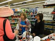 Christy Martin, center, a gemologist who works at family-owned Clater Jewelers and Diamond Center in Westport Village, answered a customer's questions as store owner Megan Campbell Martin, Christy Martin's mother, looked on. The jewelry store had a display in the Middletown Kroger store on Thursday and Friday, selling Derby-themed items.