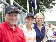 Brian Workman sits with his son Adam and his wife Teena as they watch Spain and Thailand tee off from the first hole at Caves Valley.