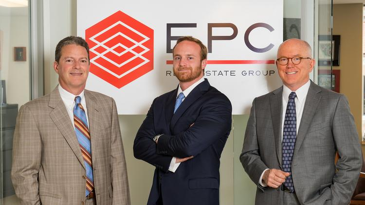 EPC Real Estate Group principals, from left, Terry O'Leary, Mike McKeen and Steve Coon are pictured with the new logo for their company, previously known as ePartment Communities.