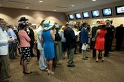 Patrons wait in line to bet in the Jockey Club Suites at Churchill Downs.