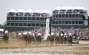 The Kentucky Derby field enters the first turn.