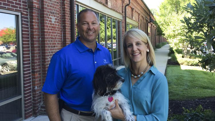 A. Brent Hinton, co-founder and vice chairman of PetFirst Healthcare LLC, and Katie Grant, CEO of PetFirst, pose with Franklin, Grant's dog.