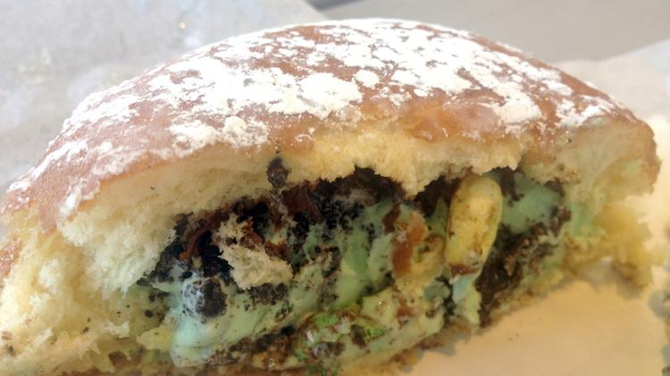 """This """"ice cream puff"""" from The Parlor features mint chip ice cream inside a glazed doughnut. The ice cream is topped with cookie crumbs, cereal and Nutella."""