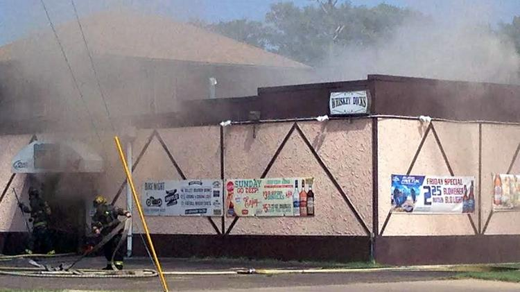 Crews work to put out a fire at Whiskey Dick's Bar and Grill on Monday.