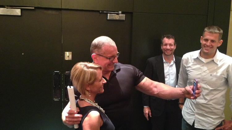 Robert Irvine takes a selfie with a fan after his speech.