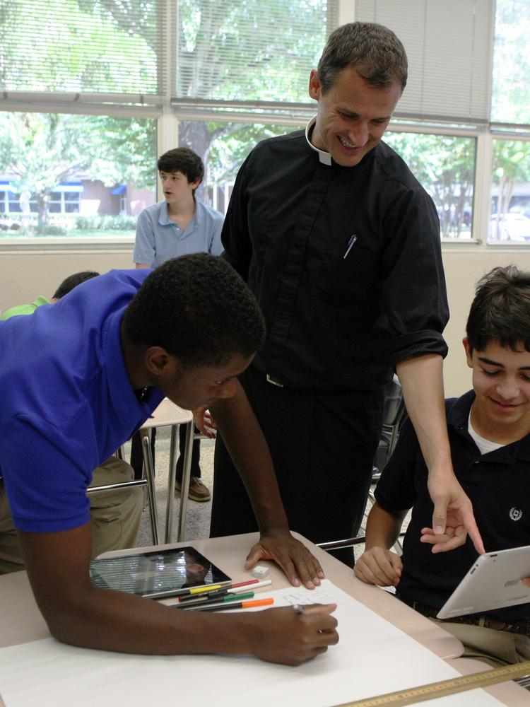 Father Hough and two students using one of the iPads provided by 1:1 Program.