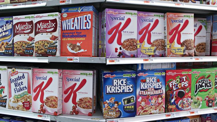 Kellogg's cereal products are displayed along with other brands in a supermarket.