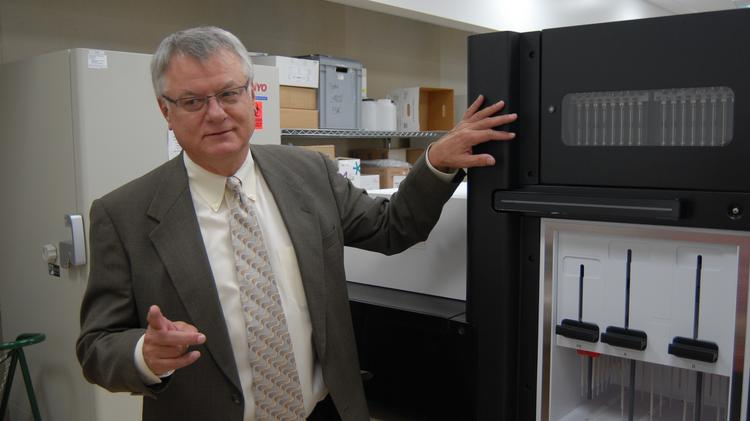 Dr. Walter Urba, research director at Providence Cancer Center, with the Illumina HiSeq 2500 system for genome sequencing.