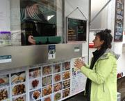 Laura Weiss, founder of GOBox, exchanges reusable containers with a food cart worker.