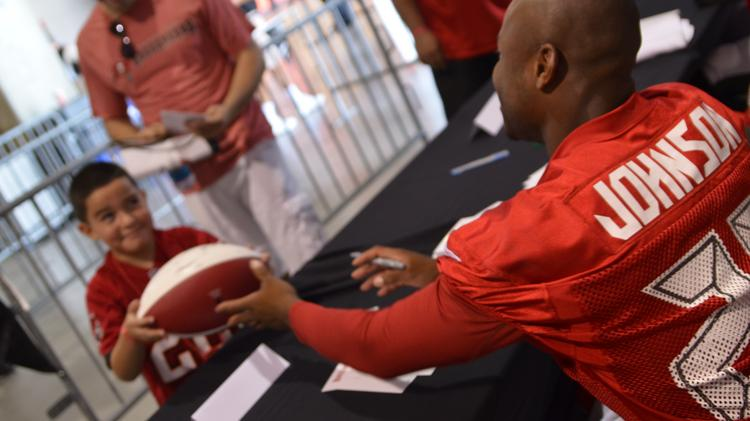 Cornerback Leonard Johnson signs a football for a young fan on Friday night at Buccaneers night practice.