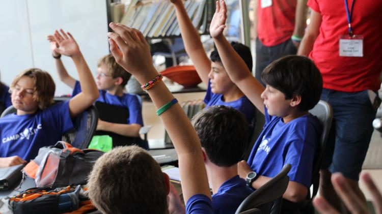 Middle schoolers ask questions as they learn about the basics of startups during a presentation at Camp Inc.
