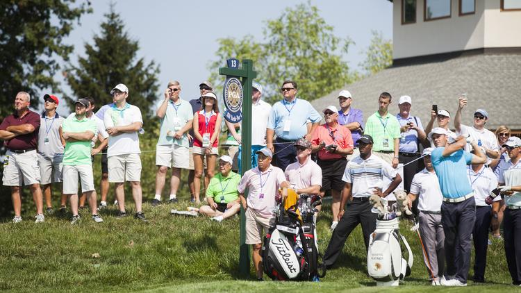 Golf fans watch as pro golfer Martin Kaymer tees off on the 13th hole during a practice round on Monday.