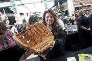 Emily Cox, of the Louisville Slugger Museum & Factory, showed a giant baseball glove to people coming by her table.