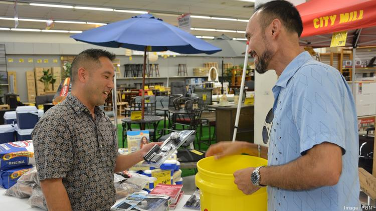Mark Kazunaga, left, and Caz Ferguson talk about the benefits of a rechargeable LED flashlight at City Mill in Honolulu. Many of City Mill's emergency items sold out on Tuesday, but the store anticipated more items to come in Wednesday.