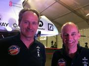 Solar Impulse pilots André Borschberg and Bertrand Piccard stand in front of the single-seat solar airplane.