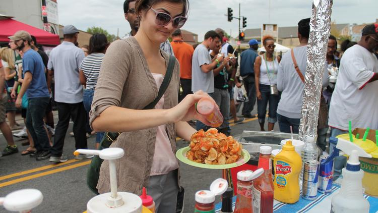"""A festival goer at a street food vendor at the H Street NE festival in 2013. H Street NE is one of the neighborhoods cited as making D.C. """"cool,"""" according to Travel Weekly."""