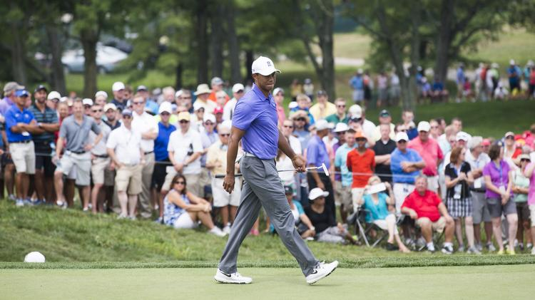Tiger Woods checks out his last putt of the day in the first round of the PGA Championship.