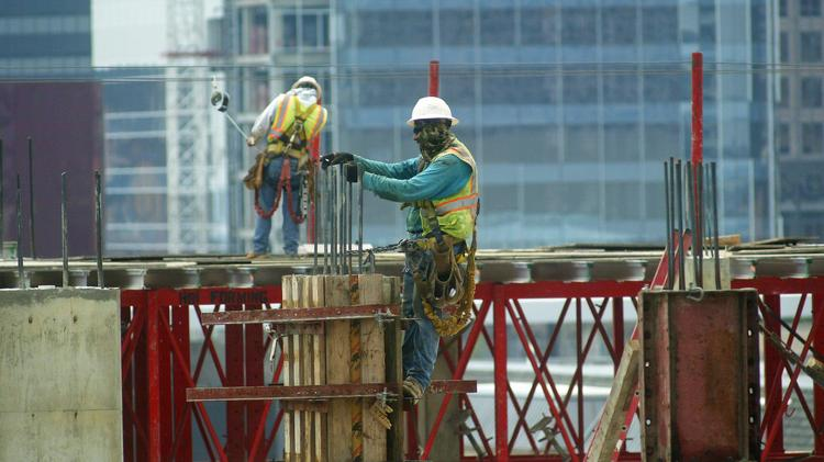 Construction workers help build a new multipurpose development in the Uptown area of Dallas.