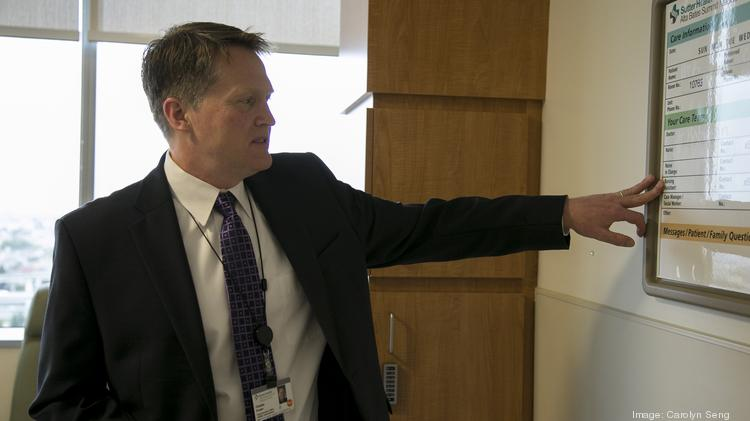 Chuck Prosper, Alta Bates Summit's CEO, shows off the whiteboard in a patient room used to inform patient and family about caregivers.