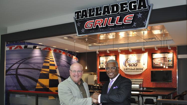 Talladega Superspeedway Chairman Grant Lynch and Birmingham Mayor William Bell celebrate the unveiling of the Talladega Grille at Birmingham-Shuttlesworth International Airport.