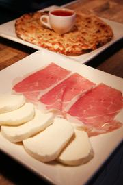 A plate of fresh mozzarella cheese and prosciutto, in the foreground, and a plate of Carta Da Musica flatbread sit on the delivery counter. The restaurant is credited with helping to revive the Columbia City neighborhood.