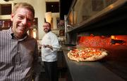 Tutta Bella founder and owner Joe Fugere, left, stands nearby as Executive Chef Brian Gojdics pulls a pizza from the oven at the Neapolitan pizzeria company's Columbia City restaurant in Seattle.