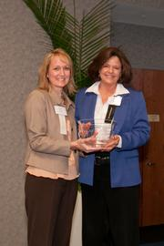 Terri Hanlon of TriHealth, left, presents a winner's award in the 100-499 employees category to Cathy Hanley, general manager of human resources for Gallatin Steel.