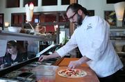 Executive Chef Brian Gojdics preps a pizza for the oven at Tutta Bella's Columbia City restaurant in Seattle. Pizzas have been delivered to President Barack Obama on a visit to Everett.