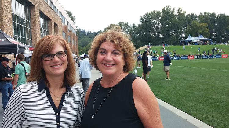 Boeing Boys and Girls Clubs of Bellevue CEO Kathy Haggart, right, and Food Lifeline CEO Linda Nageotte, left, celebrated the grant Tuesday at the Seattle Seahawks training facility.