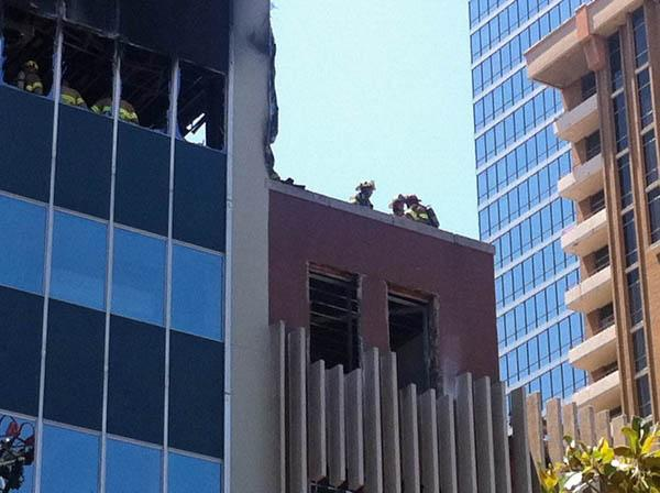 Dallas firefighters look out from the building in downtown Dallas Wednesday where they battled a three-alarm fire.