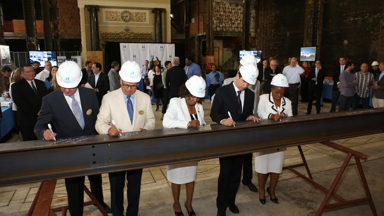 Concord President and CEO Mark Laport (left) with Tony Isaac, senior vice president of strategy and development for Hyatt Hotels Corp.; Jersey City Councilwoman Diane Coleman, Jersey City Mayor Steven Fulop and Councilwoman Joyce Watterman sign an 800-pound support beam that will become part of the new Hyatt Place hotel's foundation in Jersey City.
