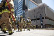 A crew of Dallas firefighters walk to the building that caught fire around noon.