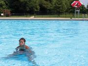 Kierra (under water) and Kayla Stanton enjoy an afternoon at the Clifton Park pool with their grandmother, who's been teaching the girls to swim.