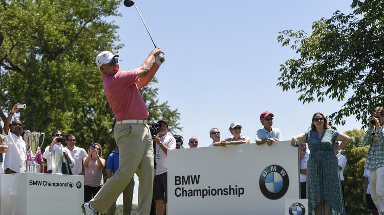John Elway tees off before the BMW Championship exhibition, a charity event held on July 22.